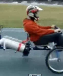 Boy riding a 3 wheel motor bike running on compressed air.
