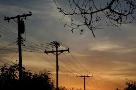 Photo of sun setting with telephone poles