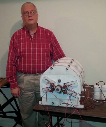 Jim Relwog standing next to Fuel-less engine sp500 generator he built