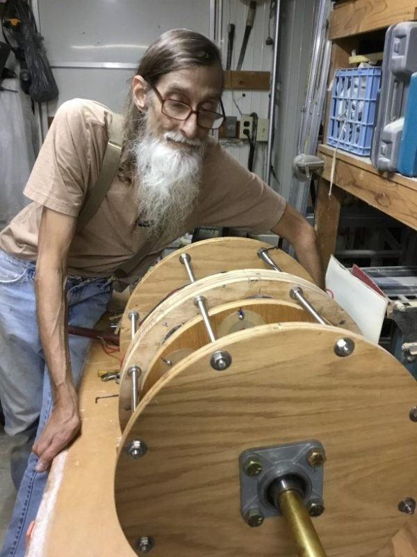 Lenny B. sitting next to his home built wooden SP500 Generator motor