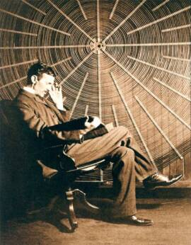 Nikola Tesla sitting in chair with large spiral coil behind him